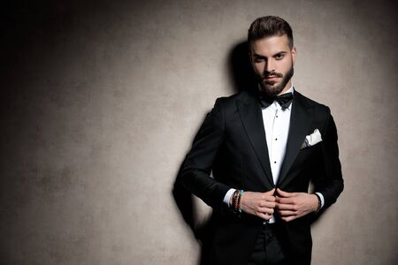 Photo pour sexy young elegant model in tuxedo adjusting coat in a fashion light on brown background in studio - image libre de droit