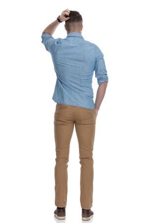 Photo pour Rear view of confused casual man scratching his head while wearing blue shirt, standing on white studio background - image libre de droit