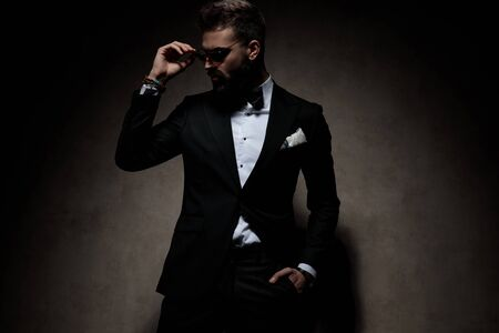 Photo pour attractive businessman wearing tuxedo standing with hand in pocket and fixing sunglasses while looking aside with style on dark sudio background - image libre de droit