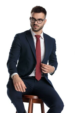 Photo for sexy businessman wearing glasses sitting while fixing jacket and striking a pose with serious attitude on white studio background - Royalty Free Image