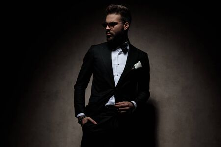 Photo for sexy businessman wearing sunglasses standing with hand in pocket and striking a pose with cool attitude on dark studio background - Royalty Free Image