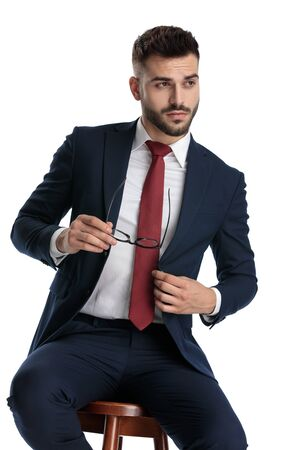 Photo pour sexy businessman wearing navy suit sitting while taking off his glasses with cool attitude and fixing jacket on white studio background - image libre de droit