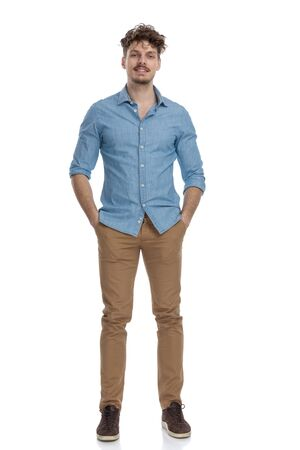 Photo pour attractive casual guy in denim shirt holding hands in pockets and smiling isolated on white background, full body - image libre de droit