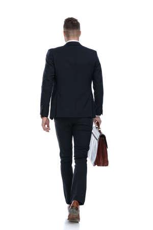 Photo pour Rear view of businessman holding briefcase and walking on white studio background - image libre de droit
