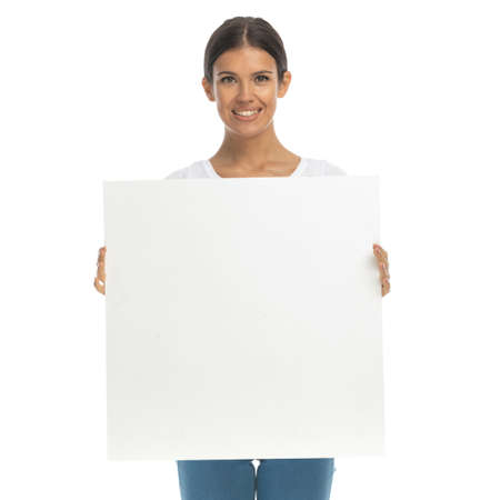 Photo pour Happy casual woman smiling and holding billboard while standing on white studio background - image libre de droit