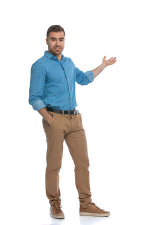 Photo pour sexy casual man sticking one hand in his pocket and presenting something to a side with the other one against white background - image libre de droit