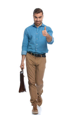 Photo pour happy casual man walking towards the camera while giving a thumbs up and holding a briefcase against white background - image libre de droit