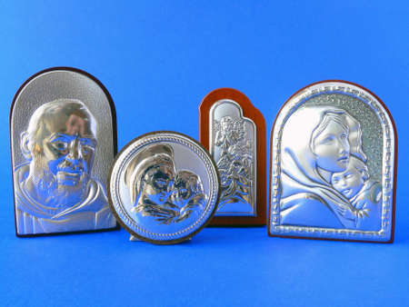 Different religious silver-plated icons over blue