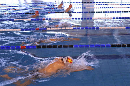 Boys swimming in a pool during a breaststroke championship