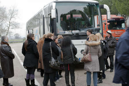 Italy - March 2010: A luxury chartered bus and some passengers during a tour in a parking area waiting for going forth. Photo taken  in a highway parking area.