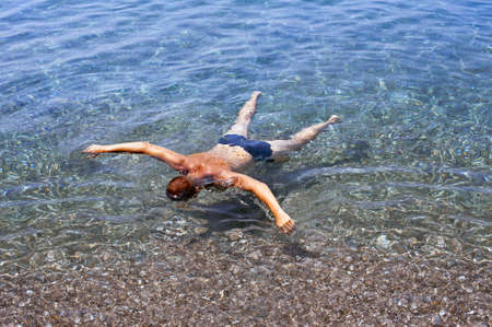 A boy swimming floating as to play dead