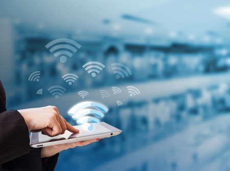 Photo pour Businesswoman connecting to Wifi - image libre de droit