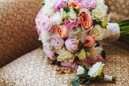 Foto de Beautiful wedding bouquet, two gold rings, boutonniere, lying on the armchair, wedding day. Important holiday accessories - Imagen libre de derechos