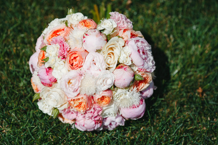 Foto de Beautiful bouquet of flowers from the magnificent flowers of peonies and roses in full bloom lying on the green grass close-up. Wedding day. Bride accessories - Imagen libre de derechos