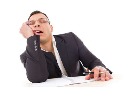 tired businessman yawning and sleeping at work with pen in hand