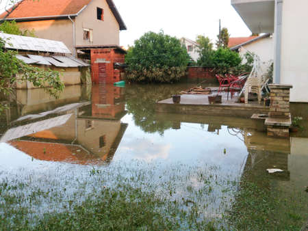 condition of house with a yard after floods, flood and disaster in town Obrenovac in Serbia, damaged houses and property, state or condition after terrible flood, destroyed and abandoned city