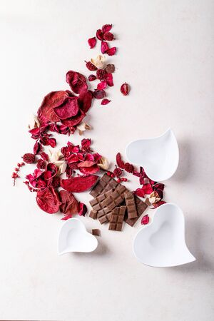Photo pour Saint valentine's day ceramic plates in shape of a heart with chocolate over white texture background. Top view, flat lay. Copy space - image libre de droit