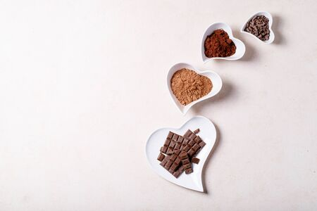 Photo pour Saint valentine's day ceramic plates in shape of a heart with chocolate and cacao over white texture background. Top view, flat lay. Copy space - image libre de droit