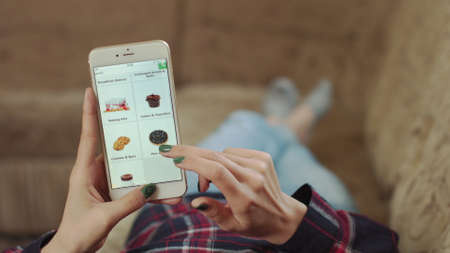 Foto de Woman at Home Lying on Couch in Living Room Using Smartphone Buys in Internet Shop. Woman Orders Bakery Home In An Online Store Using a Smartphone. Female Selects Bakery in Grocery Online Store. POV - Imagen libre de derechos