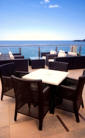 Rattan armchairs on the terrace lounge with seaview in a luxury resort .