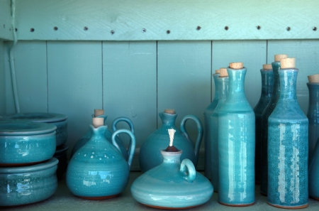 turquoise glazed ceramic pitchers in green shelf , Crete , Greece