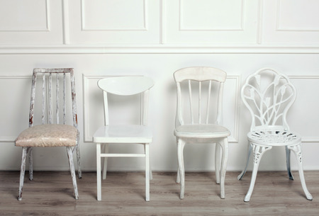 Set of white wooden vintage chairs standing in front of a white wooden wall on light parquet floor.