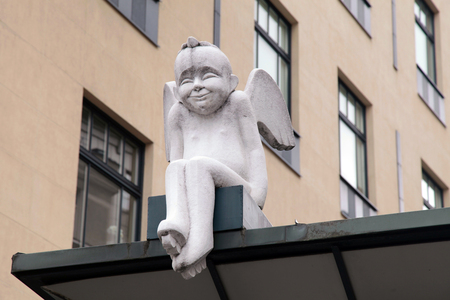 Little white angel statue sitting on the roof in Old Town, Vilnius , Lithuania