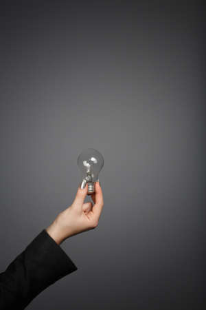 Concept with woman's hand in dark jacket holding a light bulb on grey background. Close-up.