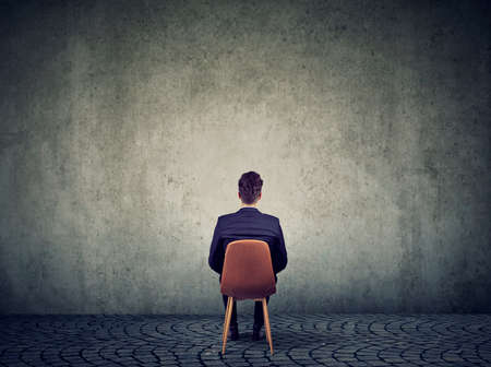Business man sitting on chair in front of concrete empty wall solving a problem
