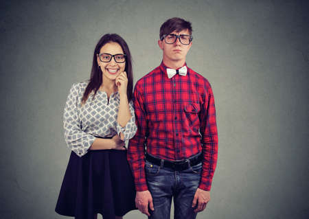 Portrait of attractive charming woman dating with nerd in old fashioned eyewear and eccentric wear. Extraordinary couple concept