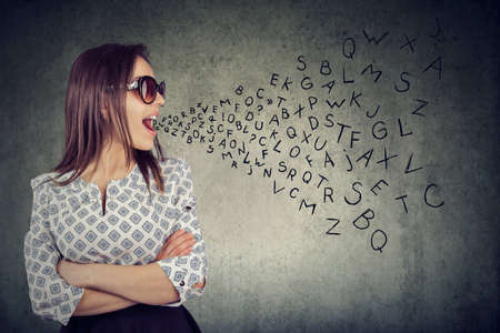 Woman in sunglasses talking with alphabet letters coming out of her mouth. Communication, information, concept