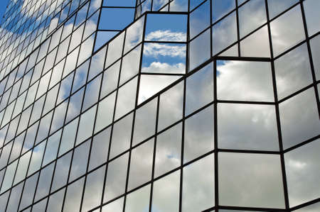 Modern glass office building with clouds and sky reflections.