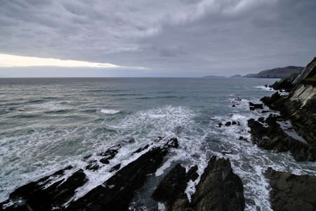 Beat of waves at rocky beach in Dingle peninsula during windy sunset