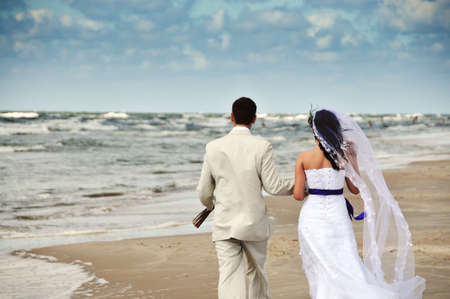 happy wedding couple walking along seashore