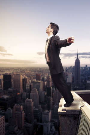 Troubled businessman letting go from the top of a building