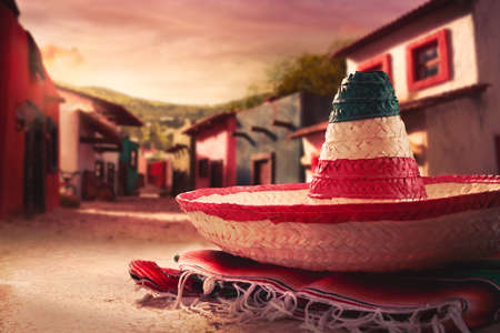 Mexican hat sombrero on a serape in a mexican town at sunset