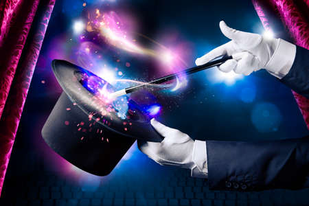 Magician hand with magic wand and hat