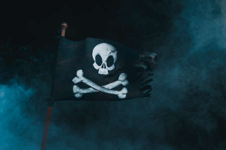 Foto de Pirate flag waving with the wind on a smoky background - Imagen libre de derechos
