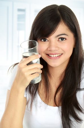 Healthy young woman holding a glass of water and smiling