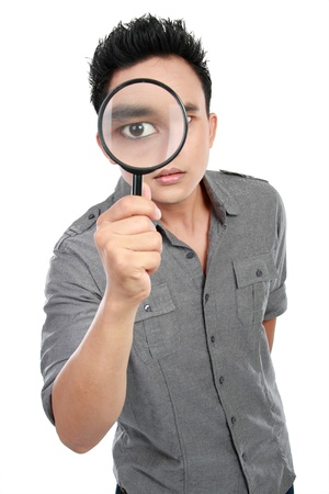 portrait of young man looking through a magnifying glass isolated over white background