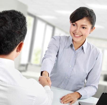 Photo pour Pretty asian business woman shaking hands with a man in her office - image libre de droit