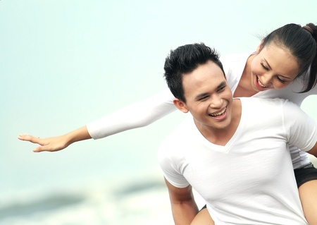 Close up portrait of a young asian man giving piggyback to woman on the beach.の写真素材