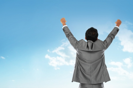Happy business man with arms raised under the blue sky