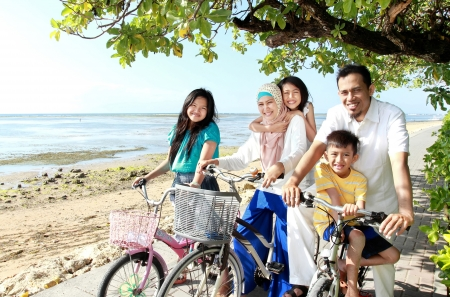 Foto de Happy asian family riding bikes in the beautiful morning at the beach - Imagen libre de derechos