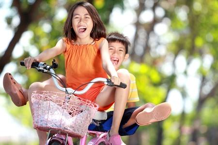 Photo pour happy smiling kids enjoy riding bicycle together outdoor - image libre de droit
