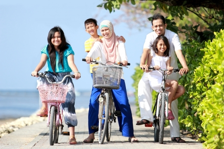 Foto de Happy asian family riding bikes in the beautiful morning at the beach - Imagen libre de derechos