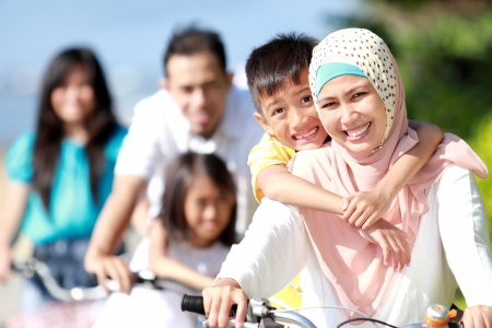 Photo pour Happy asian family riding bikes in the beautiful morning outdoor - image libre de droit
