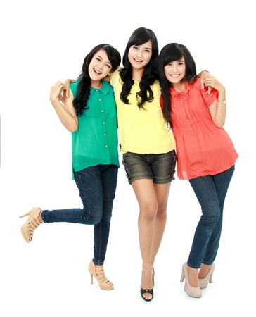 Portrait of attractive three teenage girls hugging each other isolated on white background