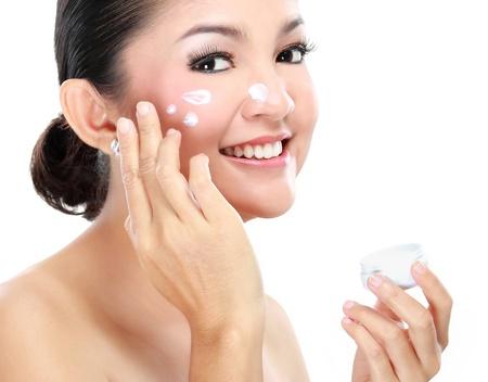 Photo pour Beautiful women applying moisturizer cosmetic cream on face - image libre de droit