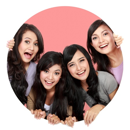 Group of beautiful women smiling peeping through circle hole. good for your designの写真素材